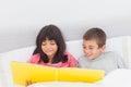 Enfants de mêmes parents dans le lit regardant ensemble leur photographie Image libre de droits