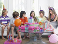 Enfants s asseyant sur sofa at birthday party Image stock