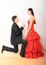 Engaged couple young men in business suit kneeing in front of young women smiling girl in red evening dress and proposing her with Stock Photos