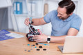 Engeneer in blue t-shirts constructing droid Royalty Free Stock Photo