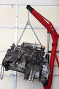 Engine in shop for rebuild a car hanging from hoist mechanic professional tear down and trade names and part numbers have been Stock Photo