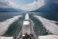 Engine and wake of motor boat speeding across lake surrounded by view power como in italy on a sunny day with cumulus clouds in Stock Images