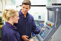 Engineer and apprentice using automated milling machine in factory Royalty Free Stock Photos