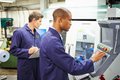 Engineer and apprentice using automated milling machine in factory wearing uniform Royalty Free Stock Photography