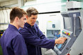 Engineer and apprentice using automated milling machine looking at dials concentrating Royalty Free Stock Photos