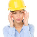 Engineer or architect woman worker having headache migraine stress wearing yellow hard hat young female mixed race caucasian asian Royalty Free Stock Image
