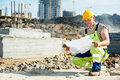 Engineer builders at construction site with draft one builder blueprint plan Royalty Free Stock Images