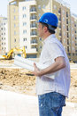 Engineer on construction site with blue hard hat holdind project the Stock Photo