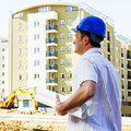 Engineer on construction site with blue hard hat holds blueprint the Royalty Free Stock Photography