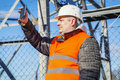 Engineer filmed with tablet pc near metal structures in autum day Royalty Free Stock Photo