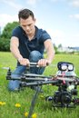 Engineer fixing propeller of uav drone young crouching while in park Stock Images