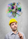 Engineer with a helmet on his head reflecting staring into the void holding pencil under her nose Royalty Free Stock Image