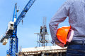 Engineer holding yellow safety helmet in building construction site with crane Royalty Free Stock Photo
