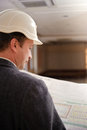 Engineer looking at plans or architect with a hard hat Stock Photos