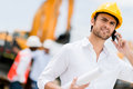 Engineer making a business call at construction site Royalty Free Stock Images