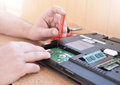 Engineer restores the laptop PC. Installing the hard drive hardware, RAM. Electronic repair shop, technology renovation