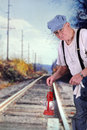 Engineer signalling train coming a senior with his red langern Stock Images