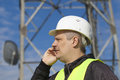 Engineer talking on the cell phone near to gsm tower Stock Photo