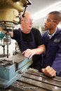 Engineer teaching apprentice to use milling machine looking at each other having a discussion Royalty Free Stock Photo