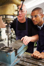 Engineer teaching apprentice to use milling machine wearing protective glasses Royalty Free Stock Photo