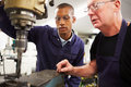 Engineer teaching apprentice to use milling machine whilst wearing uniform and protective glasses Royalty Free Stock Photos