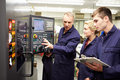 Engineer teaching apprentices to use computerized lathe looking at dials taking notes Royalty Free Stock Image