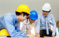 Engineer team looking paper plans at construction site Royalty Free Stock Photo