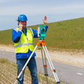 Engineer and total station or theodolite working with a modern on a tripod Royalty Free Stock Photography