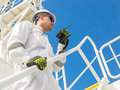 Engineer with vhf under blue sky in white helmet and workwear Stock Photography