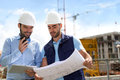 Engineer and worker checking plan on construction site Royalty Free Stock Photo