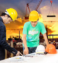 Engineer and worker man working in building construction site wi with plan equipment on table Royalty Free Stock Photos