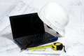 Engineering open laptop helmet and measuring tape on the drawings Royalty Free Stock Photos