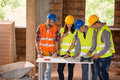 Engineers at construction site studying blue print Royalty Free Stock Photo
