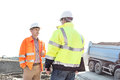 Engineers discussing at construction site against clear sky on sunny day Royalty Free Stock Photo