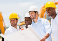 Engineers holding a blueprint working on building site blueprints Royalty Free Stock Image