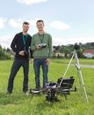 Engineers standing by uav helicopter and tripod happy young in park Stock Image