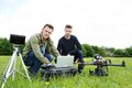Engineers using laptop by uav helicopter portrait of young and tripod at park Royalty Free Stock Photo