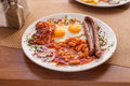 English breakfast fried eggs sausages beans traditional full and bacon on a wooden table Stock Photography