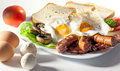 English breakfast meal two fried eggs and sausages bread salad and mushrooms Stock Image