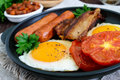 English breakfast: sausages, bacon, tomatoes, egg, beans in sauce, fried mushrooms, toast Royalty Free Stock Photo