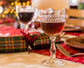 English christmas table with sherry glass in cut goblet on set for lunch crackers and decorated tree in background Stock Photo