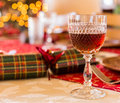 English christmas table with sherry glass in cut goblet on set for lunch crackers and decorated tree in background Royalty Free Stock Photography