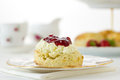 English cornish cream tea horizontal scene with scones devonshire style on china plate with cake stand behind part of a series Royalty Free Stock Photography