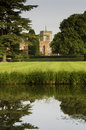 English country estate landscaping and grounds of a wealthy including a wet moat lawn and chapel belfry Royalty Free Stock Photo