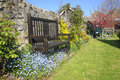 English country garden seat surrounded by flowers and spring blossom Stock Images