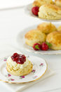 English cream tea vertical scene with scones devonshire style on china plate with cake stand behind part of a series showing the Stock Photography