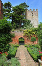 An english landscaped garden walled against a blue summer sky with church steeple Royalty Free Stock Image