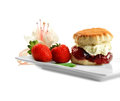 English scone a fully loaded freshly made oozing with double whipped cream and strawberry jelly against a white background the Royalty Free Stock Photo