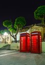 English telephone box on a summer night malta in the light of lanterns with trees Stock Photos