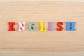 English word on wooden background composed from colorful abc alphabet block wooden letters, copy space for ad text